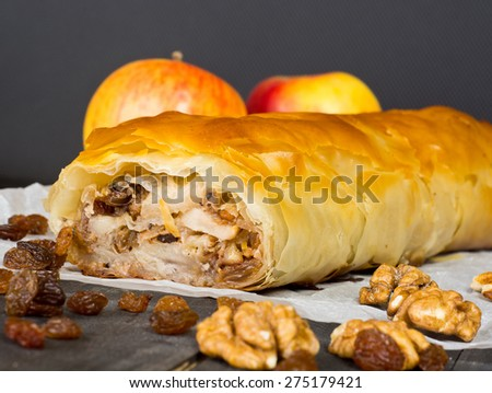 Apfelstrudel (apple pie) made of filo pastry with raisins and walnuts - stock photo