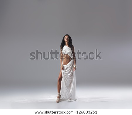 Aphrodite styled young woman over grey background with a lot of blank space - stock photo