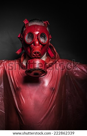 Apocalypse, A man in a gas mask over  the smoke. black background and red colors - stock photo