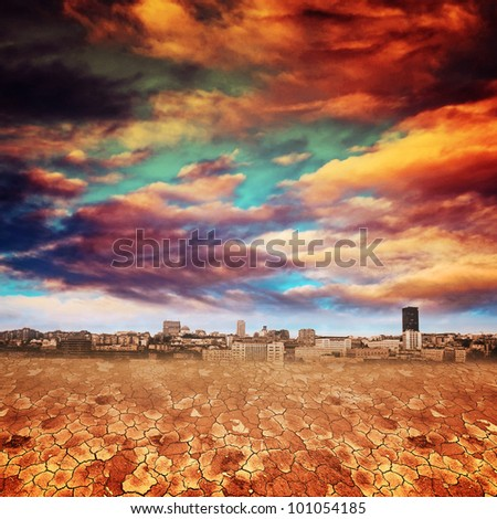 Apocalyptic landscape, global warming concept. Dry desert land against dramatic sky with heavy clouds, city in the background. - stock photo