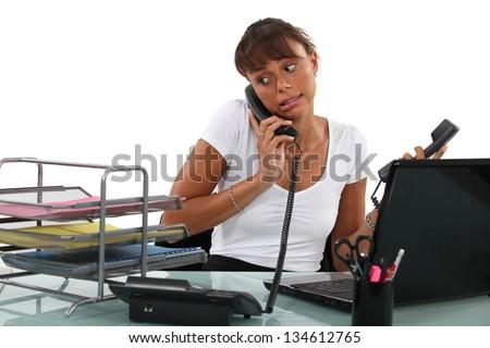 Apologetic secretary on the phone - stock photo