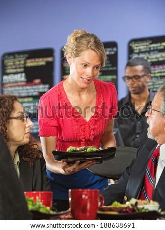 Apologetic server bringing salad to upset business man - stock photo