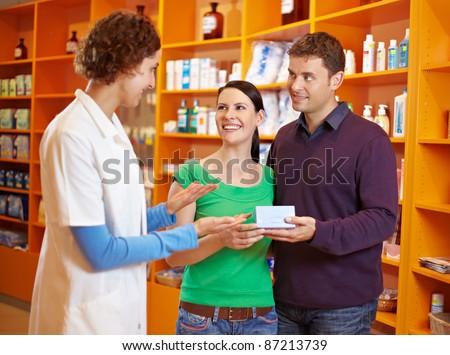 Apothekerin berät ein glückliches Paar in der Apotheke - stock photo