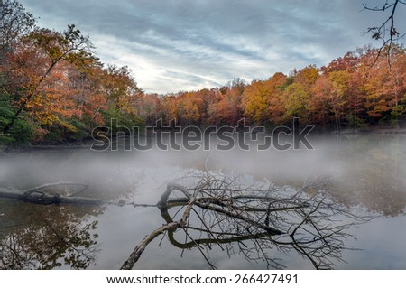 Appalachian mountain Lake in Maryland during Autumn with morning mist - stock photo