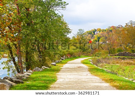 Appalachian trail along Shenandoah River near Harpers Ferry historic town in West Virginia, USA. Autumn colors of deciduous trees and scenic view on Harpers Ferry town buildings. - stock photo