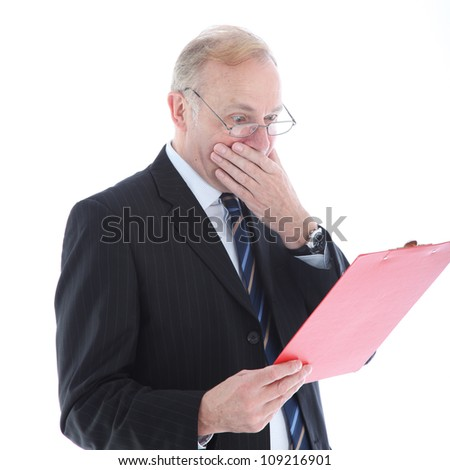 Appalled businessman reading report Appalled middle-aged businessman reading a report and covering his mouth with his hand in shock
