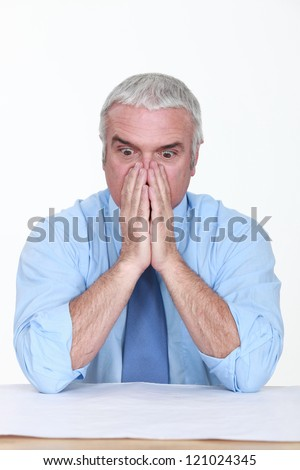 Appalled man looking at a blueprint - stock photo