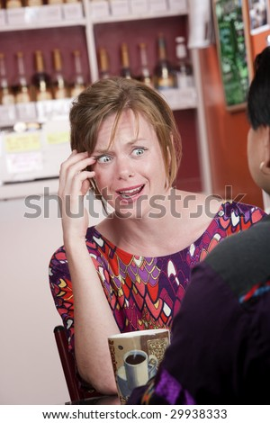 Appalled pretty woman with red hair in coffee house with male friend - stock photo