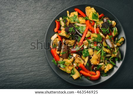 Appetizer - asian salad with eggplants, paprika and garlic on black background.