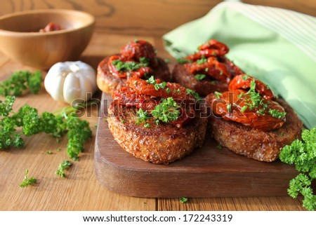 Appetizer- bruschetta with olive oil, sun-dried tomatoes and parsley - stock photo