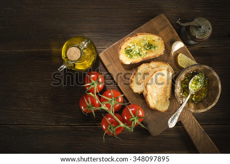 Appetizer Bruschetta with sauce of olive oil, garlic and herbs.  - stock photo