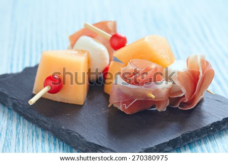 Appetizer canape with melon, cheese ball and prosciutto