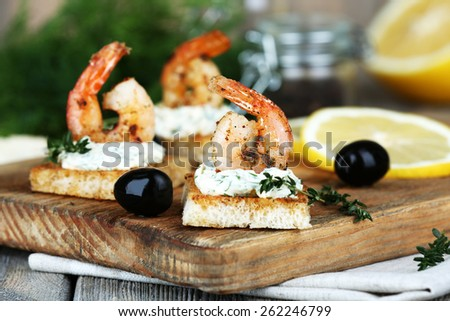Appetizer canape with shrimp and lemon on cutting board on table close up - stock photo