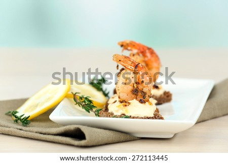 Appetizer canape with shrimp and lemon on table on light background - stock photo