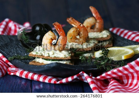 Appetizer canape with shrimp and olives on plate on table close up - stock photo