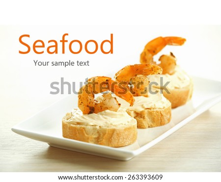 Appetizer canape with shrimp on plate on table close up - stock photo