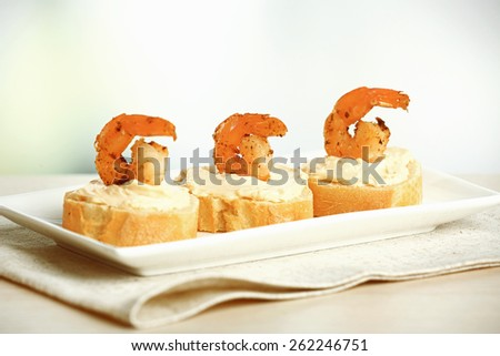 Appetizer canape with shrimp on table on light background - stock photo