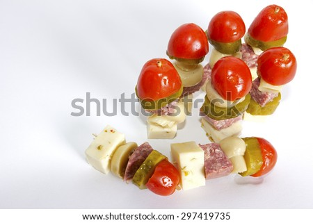 Appetizer consisting of sticks with cheese, sausages, pickles, marinated mushrooms and tomatoes.  - stock photo
