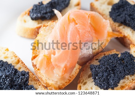 Appetizer of crostini with salmon and caviar on a ceramic plate over a white background
