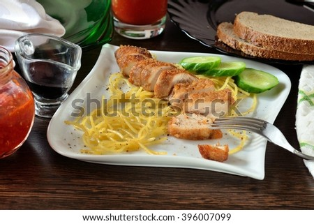 appetizer of fried chicken, spaghetti and cucumber on a white plate - stock photo