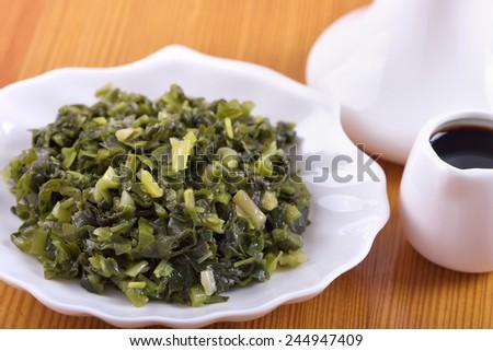Appetizer of marinated wild garlic (Allium ursinum) - stock photo