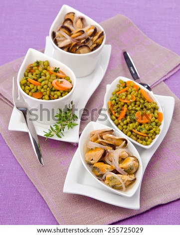 appetizer of mussels with green lentils with thyme in a salad bowl on a white lilac background - stock photo