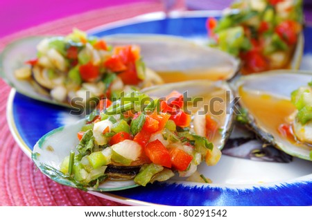 appetizer of mussels with vegetables over pink table - stock photo