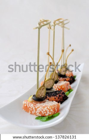 Appetizer of salmon in sesame, olives, lemon and capers
