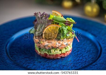 Appetizer of salmon. Salad. Tartar. Close-up in a blue plate on the table.