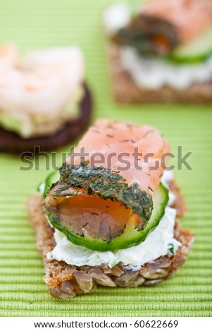 Appetizer of smoked salmon, cucumber and cream cheese on a slice of brown bread. Shallow DOF - stock photo