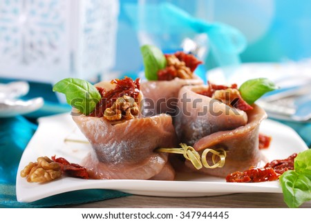 appetizer of spicy herring rolls with dried tomato and walnuts on christmas table - stock photo