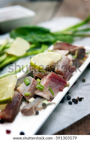 Appetizer of spicy herring with lime and onion. - stock photo