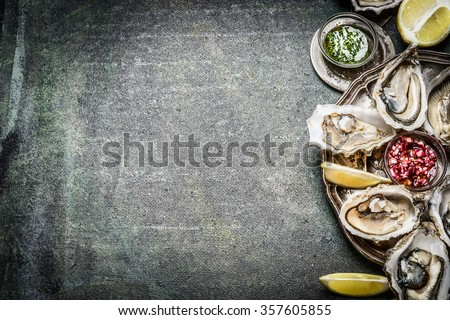 Appetizer Oysters plate with lemon and sauces on rustic background, place for text - stock photo