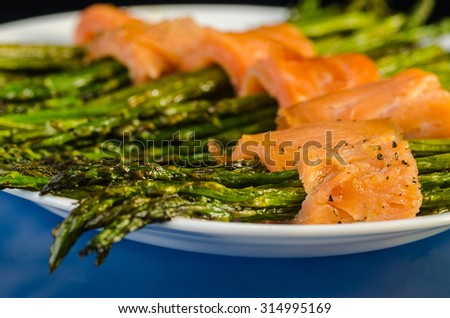 Appetizer plate of sauteed asparagus wrapped in thin slices of smoked salmon.  Closeup with selective focus and shallow depth of field. - stock photo