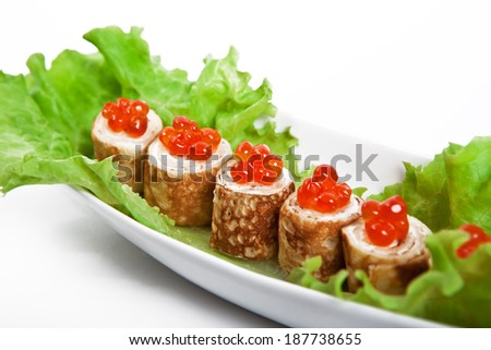 Appetizer. Rolls of thin pancakes with cream cheese cheese and red caviar - stock photo