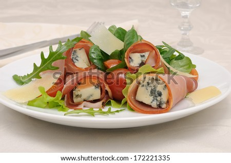 Appetizer rolls with jamon, blue cheese in the mix of lettuce and parmesan slices under - stock photo