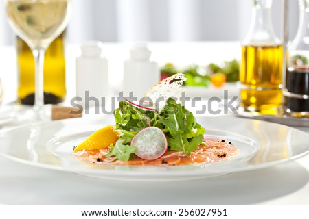 Appetizer - Salmon Carpaccio with Parmesan Cheese and Rucola - stock photo
