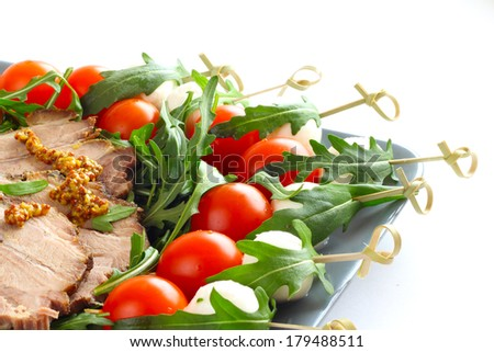 Appetizer snacks with sliced roasted meat, mozarella, tomato and arugula on white - stock photo