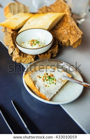 Appetizer with bread, cheese spread, chive and tiny cornflake, plate, knife, wooden bowl and glass on blue table, nice dining, food styling,closeup. - stock photo