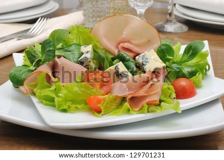 Appetizer with ham and blue cheese in lettuce leaves with corn salad - stock photo