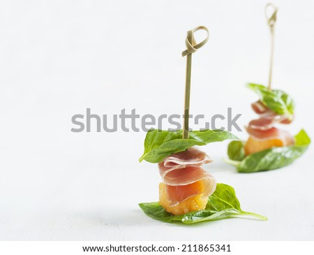 Appetizer with melon and prosciutto on skewers - stock photo