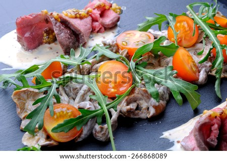 Appetizer with mushrooms, meat and tomatoes