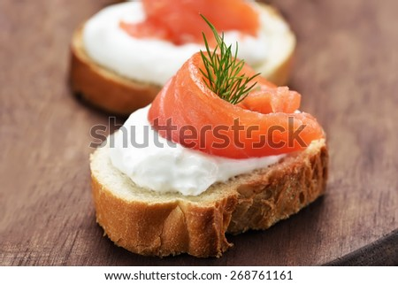 Appetizer with salmon on wood, close up view - stock photo