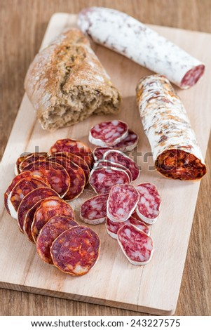 Appetizer with slices of sausage (chorizo) and bread - stock photo