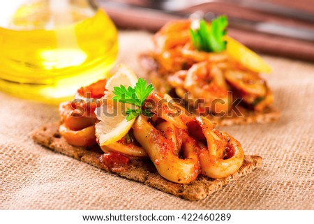 Appetizer with spicy tomato squids and lemon on toast - stock photo