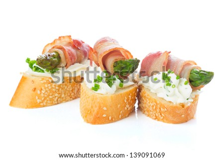 appetizers - bread slices with bacon, asparagus and soft cheese isolated om white background - stock photo