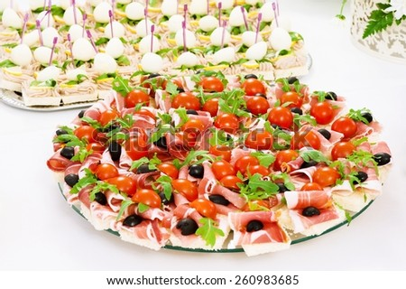 appetizers canapes ham on bread and olives and tomatoes - stock photo