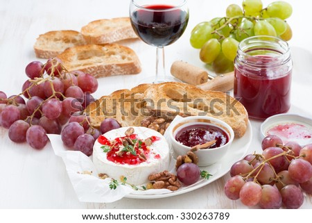 appetizers for wine - camembert with berry jam, toast and fruit on white table, close-up - stock photo