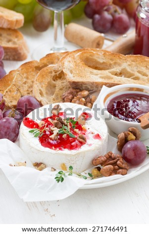 appetizers for wine - camembert with berry jam, toast and fruit, vertical, close-up, top view - stock photo
