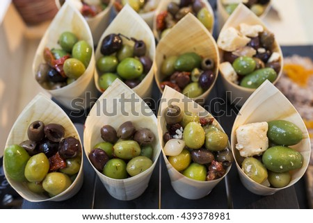 Appetizers from green and black olives, dried tomatoes, pickled garlic and cheese. - stock photo